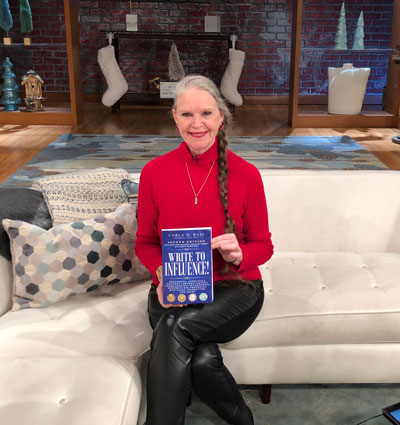 """Carla D. Bass, holding her book """"Write to Influence!"""" on set of Great Day Washington. Discussion included her services such as private coaching."""
