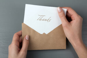 Person holding a thank you note, a critical tool to land a job following a job interview