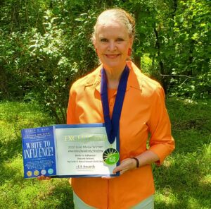 The secret to success is powerful writing. Carla D. Bass, poses with her multiple award-winning book, Write to Influence!